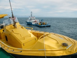 Oil research and exploration seismic vessel or ship in sea and yellow boat at another ship on foreground