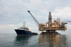 Oil rig being tugged in the sea