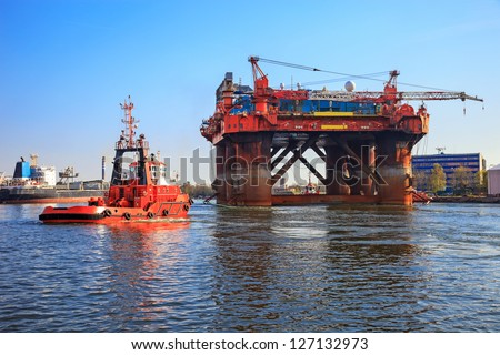 Oil rig in the company of a tug boats enters a port.