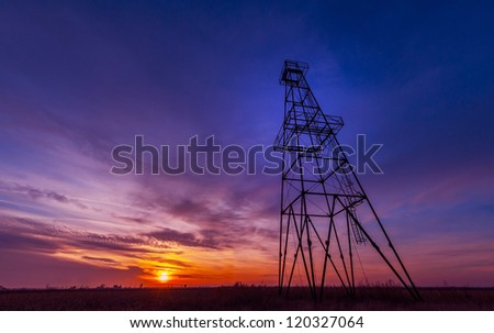 Oil rig profiled on dramatic sunset sky