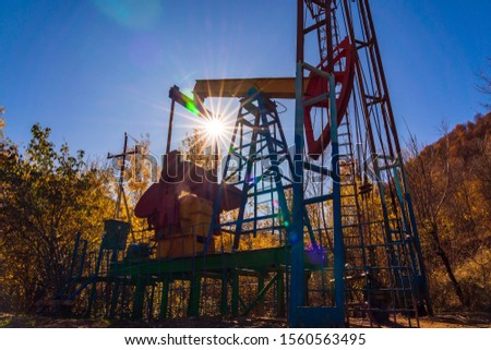 Oil rig pumps in a autumn woodland