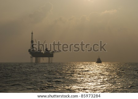 Oil rig with standby boat in the ocean