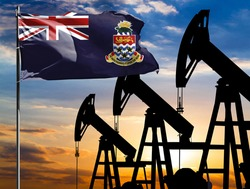 Oil rigs against the backdrop of the colorful sky and a flagpole with the flag of Cayman islands. The concept of oil production, minerals, development of new deposits.