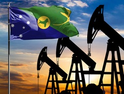 Oil rigs against the backdrop of the colorful sky and a flagpole with the flag of Christmas Island. The concept of oil production, minerals, development of new deposits.