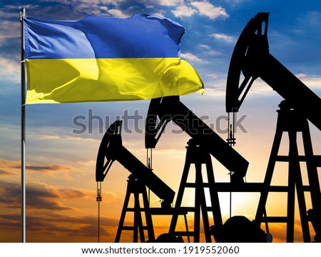 Oil rigs against the backdrop of the colorful sky and a flagpole with the flag of Ukraine. The concept of oil production, minerals, development of new deposits. Сток-фото ©