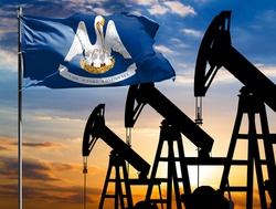 Oil rigs against the backdrop of the colorful sky and a flagpole with the flag State of Louisiana. The concept of oil production, minerals, development of new deposits.