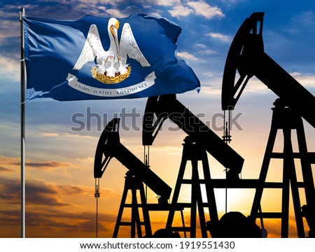 Oil rigs against the backdrop of the colorful sky and a flagpole with the flag State of Louisiana. The concept of oil production, minerals, development of new deposits. Сток-фото ©