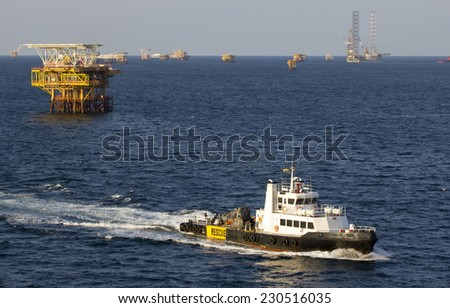 Oil rigs with standby boat for transporting people to nearby rigs