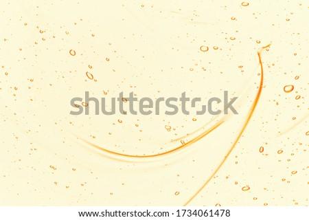 Oil serum texture. Yellow vitamin C, vitamin E liquid gel. Cosmetic cream with bubbles smear smudge. Beauty skincare product macro top view