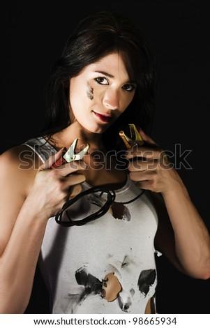 Oil stained female mechanic holding a set of power cables in her hand ready to clip them on to battery terminals for a power boost
