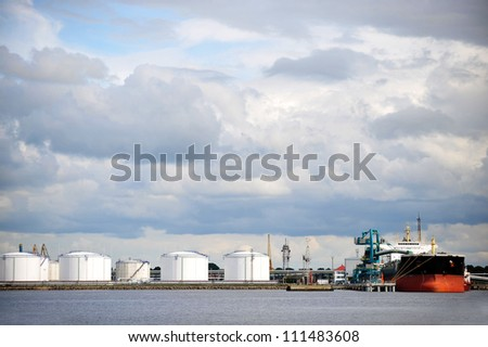 Oil Storage tanks at harbor under cloudy sky