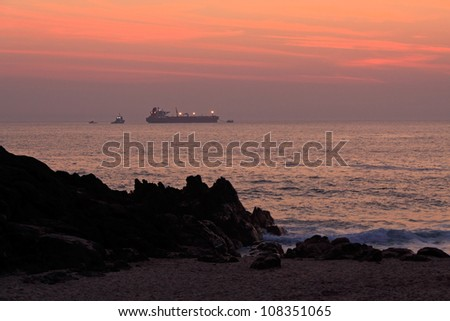 Oil tanker during unloading maneuvers off the Portuguese coast in a colorful dusk