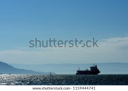 Oil tanker in backlight coming out of port with tugboat escort. City of Sao Sebastiao, Sao Paulo state, Brazil