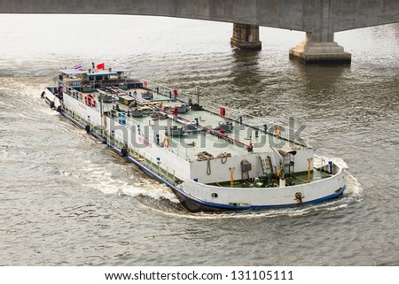 Oil tanker sailing in the river under the bridge