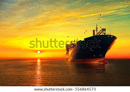 Oil tanker ship at sea on a background of sunset sky. #556864573