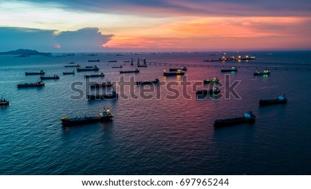 Oil tanker ship loading in port at twilight view from above.