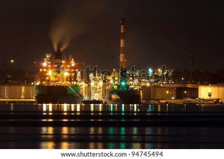 Oil tanker unloading cargo at an oil refinery illuminated at night