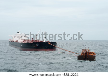 Oil tanker vessel anchored in offshore area, been loaded by some oil rig