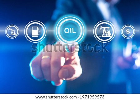 Oil trading concept. Trader holds out his finger to inscription oil. Foreground oil icons. Crude petroleum buying and selling business. Blurred hand of a trader close up. Petroleum industry Сток-фото ©