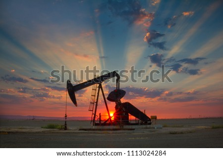 Oil well, pump jack, in the San Joaquin Valley of Central California at sunset. Oil industry background.  Stockfoto ©