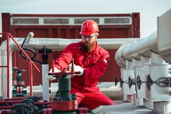 Oil worker turning valve on oil rig