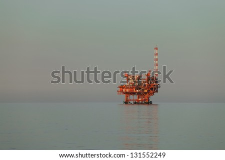oilrig lit by the rising sun