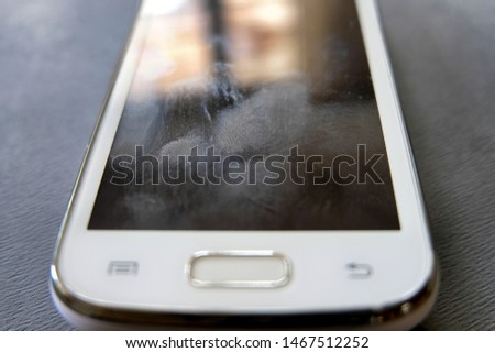 Oily fingerprint stain marks and smudges on a dirty, unclean digital smartphone touchscreen surface where build up over time can interfere or decrease touch sensitivity of the screen.