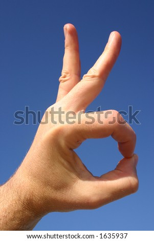 OK hand gesture with blue sky background