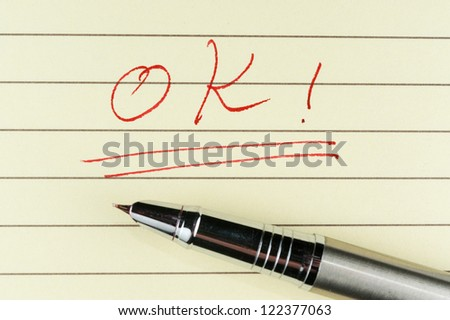 ok word written on lined paper with a pen on it