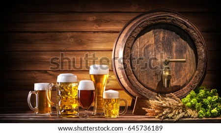 Oktoberfest beer barrel and beer glasses with wheat and hops on wooden table #645736189