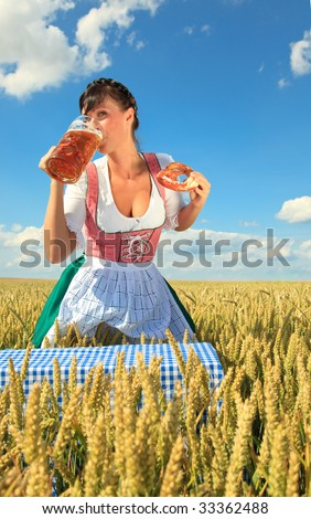 oktoberfest female waitress standing in cornfield meadow holding beer wearing traditional dirndl