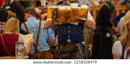 Oktoberfest, Munich, Germany. Waiter with traditional costume serving beers, closeup view Zdjęcia stock ©