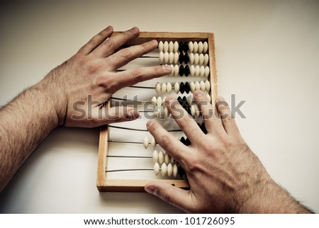 old abacus with human hand