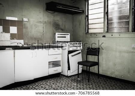 Old abandon rundown kitchen - cupboards, draws, stove, windows