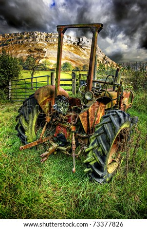 old abandoned agricultural tractor rotting away with the eglwyseg limestone escarpment beyond.