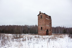 Old abandoned brick oast house in a field