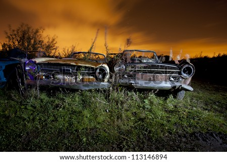 old abandoned car in a junkyard at night light painted