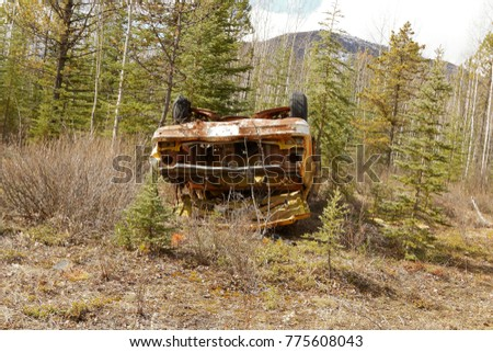 Old abandoned cars lying upside down in the bush along Alaska Highway in Canada