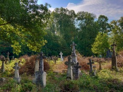 Old abandoned cemetery on a sunny summer morning. Old stone crosses on graves.