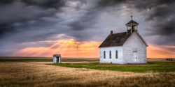Old abandoned church in the countryside at sunset. Sun rays are beaming down on the church from the clouds above. There is an old outhouse visible off to the side of the church.