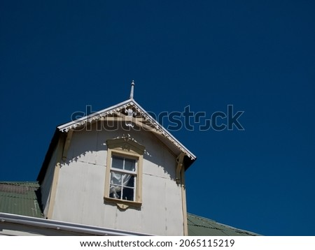 Old abandoned colonial house detail of tower with window and architectural details on a clear blue sky day