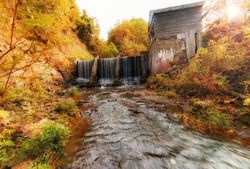 Old abandoned dam on the river in autumn. Sakhalin.