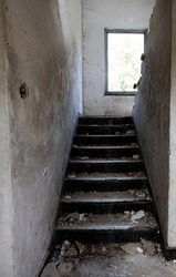 Old abandoned damaged and deserted house staircase and messy steps.