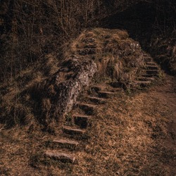 Old abandoned dilapidated stone steps in nature overgrown with moss near the mountain.