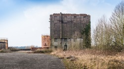 Old abandoned factory building and rusty storage tanks at a Belgian industrial area.
