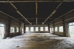Old abandoned factory building with huge windows and dirty floor