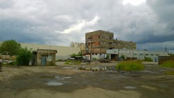 Old abandoned factory. Dirty broken road. Messy. Overcast sky. Global economic, industrial and financial crisis after coronavirus pandemic. Nobody. Workshop. Broken empty manufacturing building.