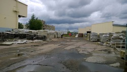 Old abandoned factory. Warehouse materials outdoors. Dirty broken road. Messy. Pits and puddles on grunge pavement. Overcast sky. Economic, industrial and financial crisis concept. Nobody. Workshop.