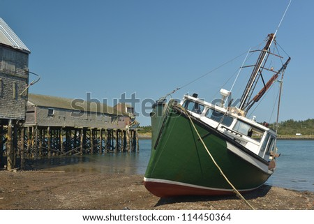 Old abandoned fish and shrimp processing wharfs and buildings at low tide on the banks of the Penobscot narrows separating Canada and the United states