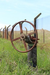 Old abandoned geared valve spindle and handle set in green grass against an old barbed wire fence and blue sky